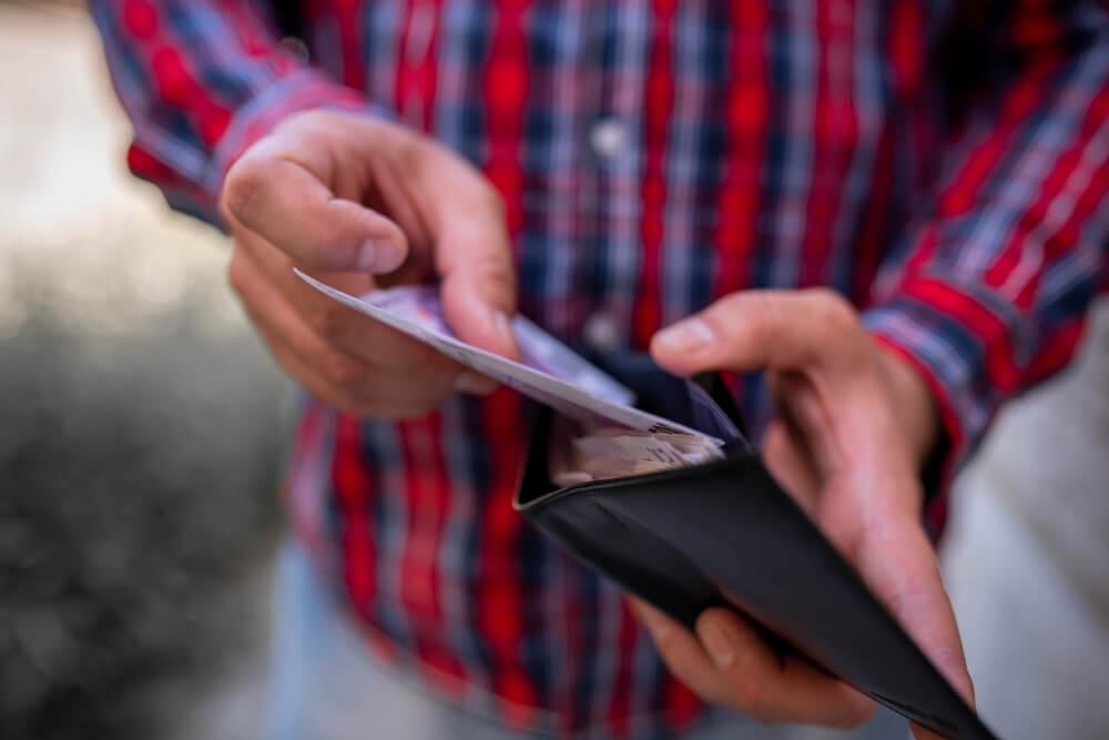 Mężczyzna liczący banknoty w portfelu - konsolidacja chwilówek w Habza Finanse
