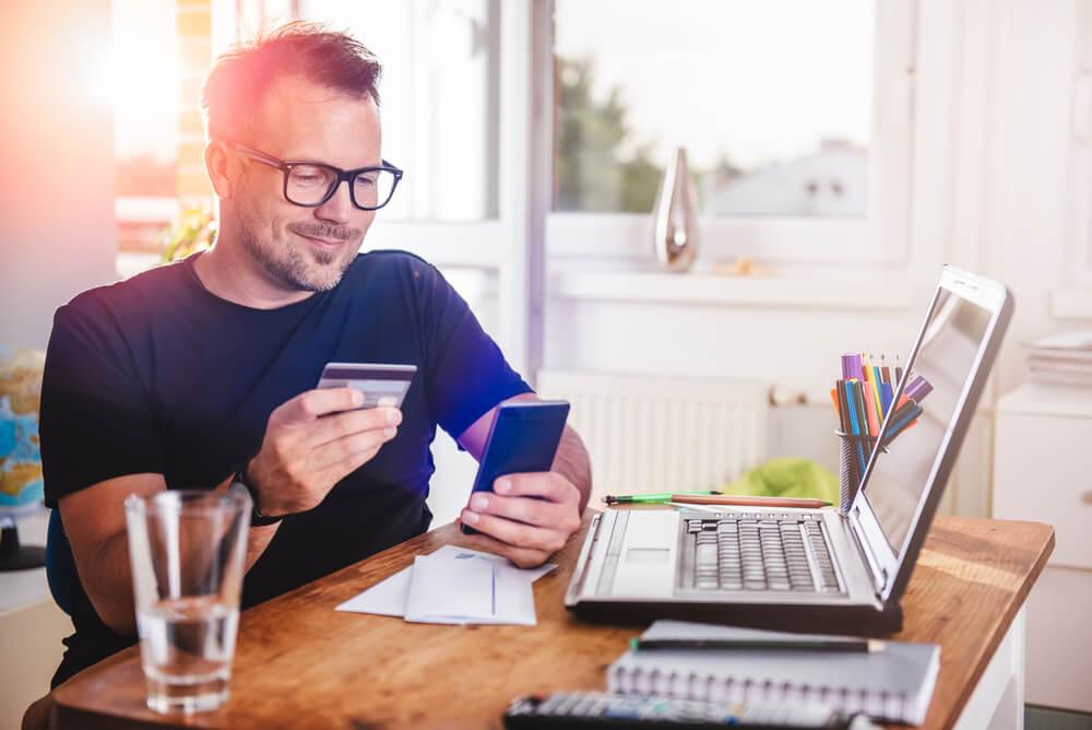Mężczyzna płacący kartą przez internet - konsolidacja chwilówek - wszystkie kedyty spłać w wygodnych ratach. Habza Finanse