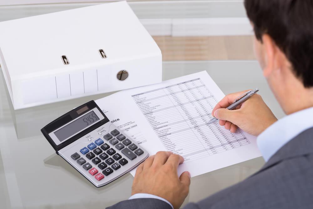 Mężczyzna analizuje swoje dochody z pomocą kalkulatora - w Habza Finanse pomogą Ci doświadczeni specjaliści skuteczna konsolidacja chwilowek i pozyczek pozabankowych - kredyty oddluzeniowe dla zadluzonych